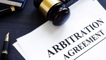 Arbitration agreement and gavel on a desk.